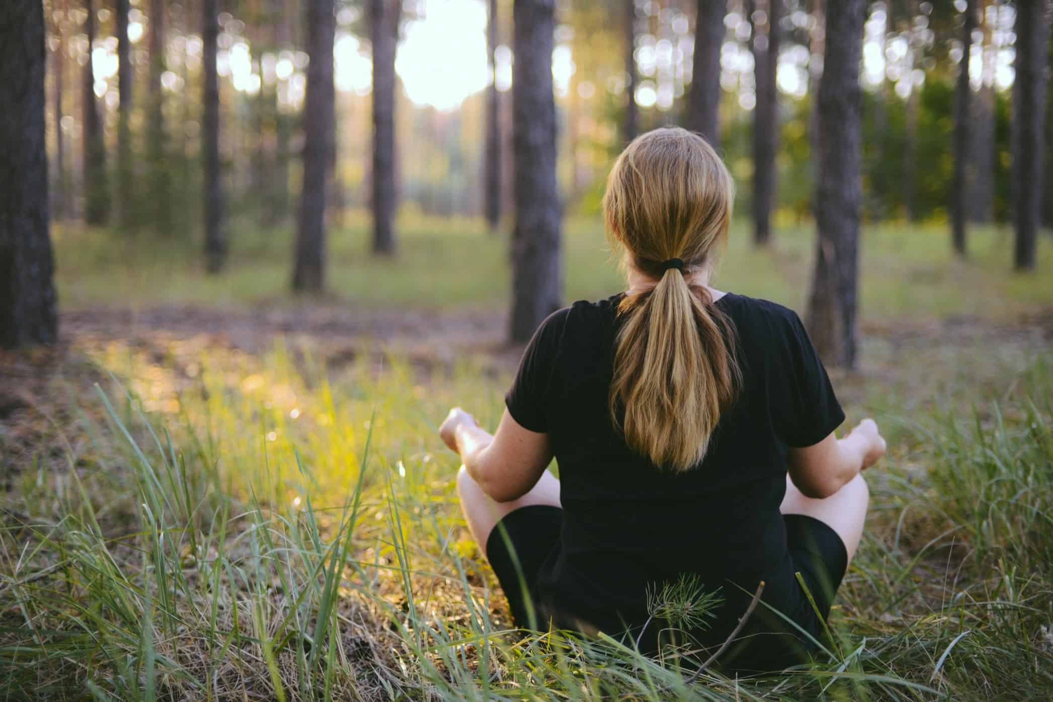 woman practices yoga and meditates in the lotus position in nature