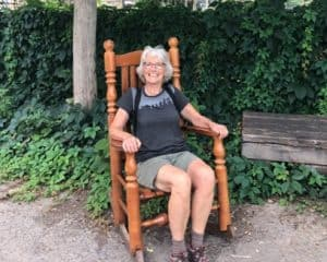 Photo of Deacon Christine Jannasch sitting on a rocking chair outside